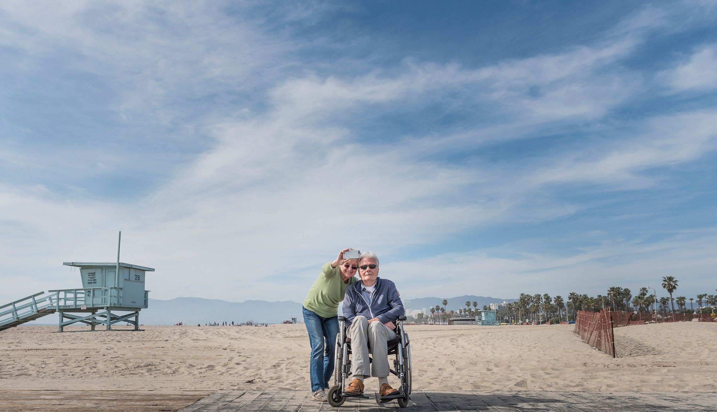 woman taking selfie with man in wheelchair on the beach